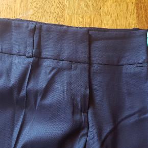 Blå bukser fra Hugo Boss i str. 42 af 60% Uld, 37% viscose & 3% Elastane  Klassiske dame Hugo Boss bukser med de klassiske pressede folder. Og en lille pyntelomme foran. Utrolig lækkert, elegant kvalitetstøj til kræsne stilbevidste kvinder.  Et pålideligt og alsidigt grundlag for et moderne business eller helt klassiske look  Se også alle de andre Hugo Boss bukser på min profil