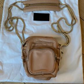 Camera bag fra Alexander Wang i Rosa med guld kæde. Tasken har kun lidt slid bag på, hvor den har været i berøring med overfladen på jakke/buks. Brugt få gange og opbevaret i dustbag. Tasken kan også afhentes i Aarhus eller Haderslev.