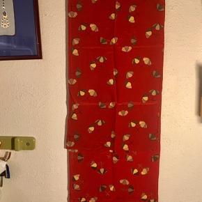 Aflangt silketørklæde med paraplyer fra Charlotte Sparre. Mærket er taget af. Farven er en blanding af mørk rust og lys bordeaux