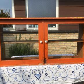 Gammelt vitrineskab med glaslåger. Det har en flot orangefarve, og vil give personlighed og charme til et hvert rum. H: 63 cm, B: 37 cm, L: 131,5 cm.