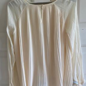 Smukkeste bluse med plisseringer på ryggen og lange ærmer. Vid facon.