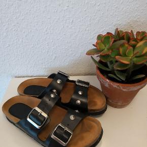 Lækre læder sandaler i sort med nitter. Modellen minder om Birkenstock. Har haft dem 1-2 gange udendørs ellers har jeg en gang i mellem haft dem på inden for. Får dem desværre ikke brugt så ofte som formodet.  ▪️Sender gerne/køber betaler porto ▪️Sender med dao  ▪️Returnerer ikke ▪️Fra dyrefrit og røgfri hjem