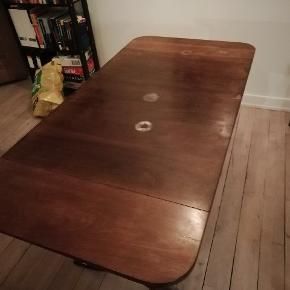 Fint lille spisebord i mørktbehandlet træ. Har nogle brugsspor, f.eks et par vandmærker, som ses på billedet. Der er plader i hver ende, som kan foldes op. Længde uden plader: 96 cm Længde med plader: 140,5 cm Bredde: 70 cm Højde: 73,5 cm