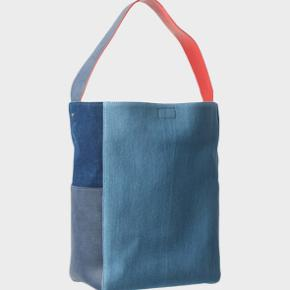 The Freja Bag is a cool take on our tote bag designed by Freja Wewer. Crafted from denim in a mix of different textures and tones, with a pop of hibiscus red calf leather. The bag features a magnet closure and interior zipped pocket.