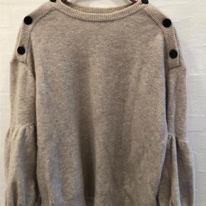 Varetype: Striktrøje Farve: Beige Prisen angivet er inklusiv forsendelse.  Meget smuk og unik strik med pose ærmer knapper langs skuldre og ærmer. Stor i størrelsen