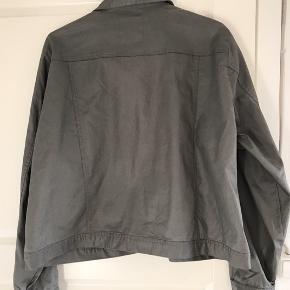 Jakke i coated stof. Brystvidde: 69 cm. X 2. Længde: 63 cm. Prisskilt: 500 kr.