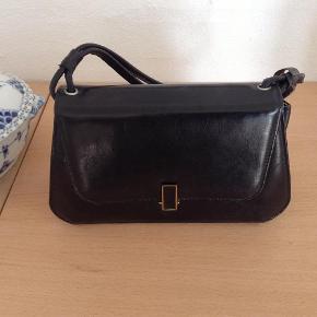 Brand: Mærke? Varetype: Antik skindtaske fra tresserne, tidligst Størrelse: Lille håndtaske Farve: Sort  Rigtig fin meget gammel håndtaske - papirer i tasken fra 1964. Sort skind med 2 små håndremme på. Lgd. 23 cm og højde ca. 13 cm. Jeg kan desværre ikke se noget mærke på tasken, men jeg kan garantere, at den er meget fin. Et arvestykke.