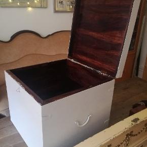Kubeformet kiste af hvidmalet mørkt træ. Måler 50,5 x 50,5 x 46 cm (længde x bredde x højde). Et håndtag på hver side til at løfte den.