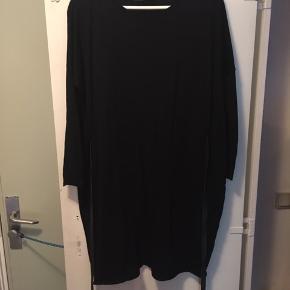Fed kjole til lige over knæet.  100% merino uld.  Læderbånd til at binde foran eller bagpå. Løs pasform. Den passes også af str. M/L
