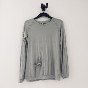 Flot grå bluse fra See by Clohé. Der er fine detaljer ved skuldrene med små stof knopper og en løs lomme i højre side.  Byd gerne :)