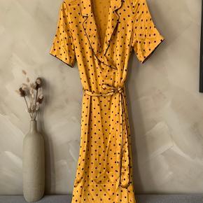 Slå-om kjole i en orange farve, med guld skær. Kjolen har en streg inde i foret, fra en kuglepen. Men ses ikke når kjolen bæres.  Mærke: Just Female  Størrelse: S  Materiale: 100% viskose