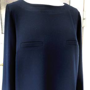 Flot enkel bluse fra Henriette Steffensen. Mørk blå. 2 snyde brystlommer. Sender gerne mod betaling af porto'en.