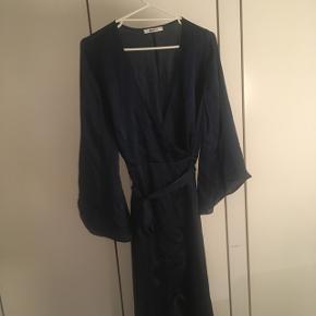 Smuk lang mørkeblå kjole i silkeagtig stof. Flot nedringet og med bånd til at binde i livet.