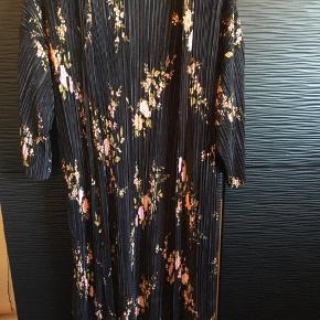 Utrolig fin kimono fra New Look i London. Tre-kvart lange ærmer, plisse look, sort med flot blomstermønster.  Jeg er 1,70 høj og den går mig til midt på skinnebenet.