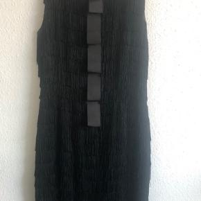 Virkelig fin sort By Malene Birger kjole i silke med smukke frynser.  Jeg sælger den billigt, da jeg har måtte fikse et par af frynserne, som har været gået op. Se billeder for eksempel. Det er kun noget man ser, hvis man virkelig går på opdagelse i detaljerne.
