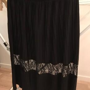 Plisse nederdel med blonde detaljer. Taljemål: 84 cm. Elastik i taljen. Længde: 71 cm