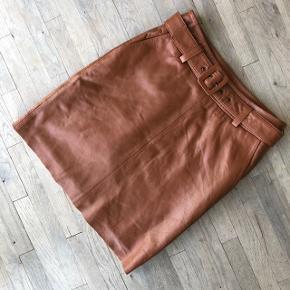 Smuk nederdel i skind. Med bælte i livet og lommer. Høj i taljen. Måler 49 cm i længden.  Har ikke tegn på slid.   Sender gerne på købers regning 🚛  ‼️SE OGSÅ MINE ANDRE ANNONCER‼️