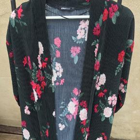 Fineste, lette 'jakke' fra Gina Tricot. Blomsterprint på fint riflet stof. 107 cm lang, målt midt bag på. Både S og M kan snildt passe den.  Helt ny.  Klik på foto ved 'mød sælgeren', og se alle mine fine ting🌸