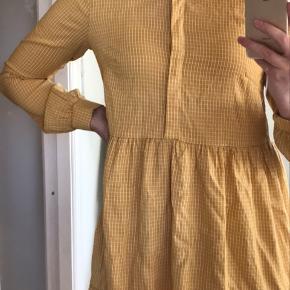 Den er ALDRIG brugt eller vasket, og har stadig prismærket på.  Kjolen er ternet gul/hvid