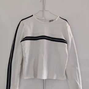 Hvid sweatshirt med sorte striber ned af ærmerne og på tværs af brystet.