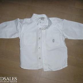 Varetype: Skjorte med bamse Farve: Hvid  Fin bomuldsskjorte med knappe ved flippen samt broderi af bamse på brystlomme.