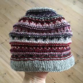 Håndstrikket hue i grå, lilla og lyserøde farver.  100% Uldgarn  Damestørrelse.  Prisen er fast.