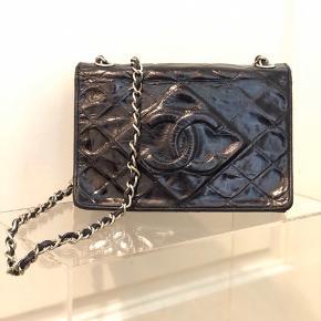Mindre sort Chanel taske 5500kr . Den har netop fået frisket den sorte farve op, hvilket gør at den igen står rigtig flot og har mange år i sig endnu! Tasken er produceret mellem 1989-1990.   Tasken har meget let slid på hjørnerne, noget der ikke er tydeligt efter opfriskning af farven. Derudover har den slid ved lukning på den ikke synlige del (se billeder) og har misfarvning på indersiden, som sikkert er pådraget da den fik opfrisket den sorte farve sidste gang (af tidligere ejer). Til denne taske medfølger der ingenting, hvilket prisen også afspejler.