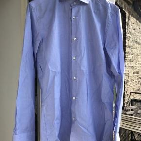 Hugo Boss skjorte i slim fit str 39. Mp 350 kr. Næsten som ny, dog har der været en lille hjemmesygning ved den ene knap. Intet der kan ses, men selvfølgelig værd at nævne, og flere billeder sendes. Kan sendes på købers regning eller afhentes på Østerbro.