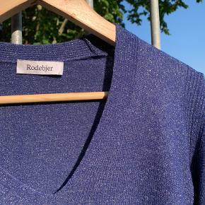 Mørkeblå, tynd striktrøje fra Rodebjer med slidser i ærmerne. Bemærk at trøjen glimter meget mere end det kan ses på billederne.   Mål: Skulderlængde: 53 cm Længde fra v-hals: 34 cm