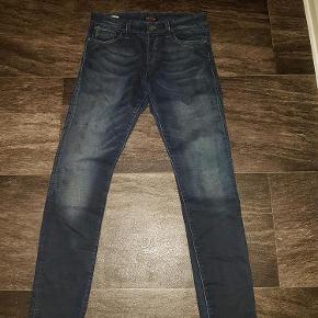 """Varetype: Jeans e31 L32 kr100 som nye slim for Glenn Størrelse: 31""""/32"""" Farve: Mørkeblå Oprindelig købspris: 600 kr.  Sender med Dao. W31 L32 Uden huller og slid Med stretch Knap lukning Livvidde 82 cm men kan strækkes til 86 cm Iindvendig benlængde 80 cm Fuld længde 106 cm Mørkeblå"""