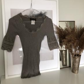 Smuk t-shirt fra Rosemunde - brugt meget få gange, står som ny og fejler intet.  Farven er meget smuk grå/ brun. 70% ren silke.  Pris fra ny lyder 449,-  Købes stadig på nettet til ovenstående pris.