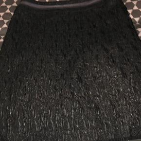 Varetype: Kort nederdel Farve: Sort  Meget flot Eva & Claudi nederdel med leopardfoer (lille revne i foret). En virkelig kvalitetsnederdel og så fin  Nederdelen er sort i lækkert stof med fine detaljer . Lille lomme bagpå i venstre side samt bånd påsyet nederst på nederdelen. Samme bånd sidder lige neden for taljen. Slids bag til op en lille slids i højre side. En meget lækker nederdel.længde ca 59 cm. Livvidde 2 x 42 cm. 66% acetat, 20% polyester - polyamid og elastan. Lækkert og flot stof.