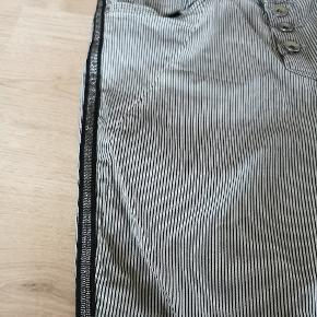 Fede jeans med 3% stræk og den smukkeste piping på siden af benene. Bundfarven er lysegrå og striber sorte. Lav talje og tight fit. Brugt 3 gange og fremstår i rigtig flot stand.