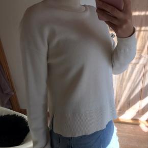 Lækker uld strik fra other stories. Striktrøjen har små slids i begge sider og høj hals.  Kradser ikke og har er meget behagelig fit.