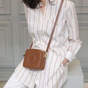 Denne lækre bomuldsskjorte, som kan bruges til enhver lejlighed, er skåret i en klassisk, lang silhuet prydet med en elegant krave og brede manchetter. Stylen fungerer både perfekt sammen med et par skræddersyede bukser eller et par jeans. Materiale: 100% bomuld. Mål str. 34: bryst 52,5cm, længde 82,5cm, ærmelængde 82,5cm, bundvidde 52cm.  Nypris 1600kr.
