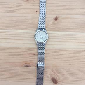 Varetype: Ur Størrelse: 34 Farve: Sølv Prisen angivet er inklusiv forsendelse.  Omega De Ville Quartz. Fedt vintage Omega ur i rigtig pæn stand.  Det måler 34 mm - meget tyndt og elegant. Der medfølger original æske.