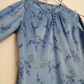 Vintagekjole i blomstret stof. Der er stræk i stoffet, lynlås i ryggen og med mulighed for at tilføje et bælte. Blankt satin-agtigt stof. Vil kunne passes af M og L.