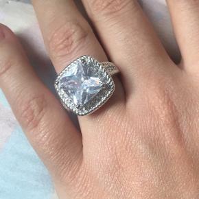 Fuldstændig vidunderligt smuk ring, desværre købt for stor. Ringen har en stor facetslebet sten i midten og små sten omkring og på siderne.