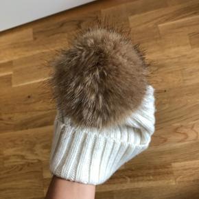 Fineste hvide hue med pelslignende detalje   Str. Onesize  Materiale: 80% polymide, 20% uld  Den er blød og varm - altså, den kradser ikke!
