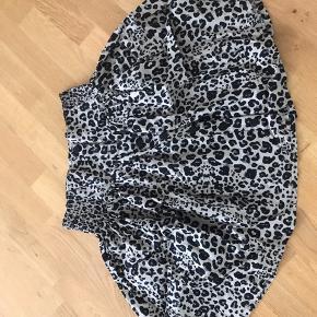 Knælang asnit nederdel fra Monki str. M. Farven er beige med sorte/grå leopard print. Nederdelen er aldrig brugt. Husker ikke nypris.