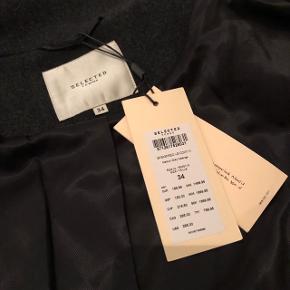 Elegant frakke fra SELECTED FEMME sælges. Frakken har ALDRIG været brugt og er stadig med prismærke.  - Figursyet - Str. 34 - Mørkegrå  Nypris: 1500kr Sælges: 550kr