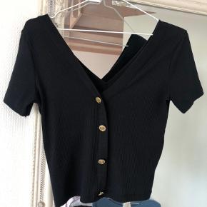 Denne sorte t-shirt med guld detaljer er kun brugt enkelte gange :)
