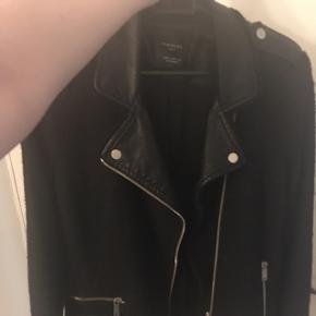 Jeg sælger denne fede Zara frakke i sort med læderlignende detaljer samt uld design. Kan tjekke om det er ægte uld hvis der er interesse for det. Det er en str M men den er lille i størrelsen, så den vil formentlig være bedre til en str S. og derfor har jeg sat den til denne størrelse.   Jeg byttede mig til den herinde på Tradono men da den er for lille til mig, sælges den videre. Ejeren før mig havde brugt den en del og det eneste slid der er at se, er det man kan se på sidste billede i nakken/ved mærkatet, der er noget af materialet skallet af men det er ikke rigtig noget man vil kunne lægge mærke til da det jo som sagt er i nakken. Frakken har været til rens, så den er helt fri for røg lugt og er ellers en rigtig fin frakke der sælges billigt som man kan se pga. det omtalte slid i nakken.  Hvis den skal sendes, betaler køber fragt.  Mvh Betina Thy