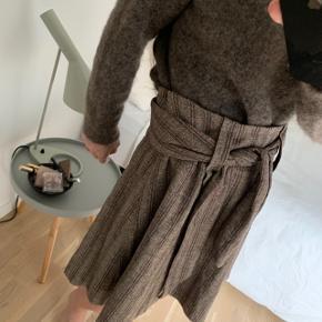 Nederdel i tweed fra Heartmade, den har et indvendigt skørt så den ikke klør. Der er skjult lynlås i siden. Længde målt foran på midten, ca. 52 cm. Indvendig livvidde ca. 78 cm.  88% Virgin wool, 10% silke, 2% Elacthane.  Bytter ikke!