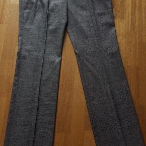 Nistret grå bukser fra Hugo Boss i str. 42 af 65% uld, 33% silke & 2% elastan  Klassiske vide dame Hugo Boss bukser med pressefolder i flot gråmeleret nistret. Str. 42, aldrig brugt, 65% uld, 33% silke & 2% elastan  2 skrå lommer på fronten & 2 pyntelomme bag på  Se også alle de andre Hugo Boss bukser på min profil