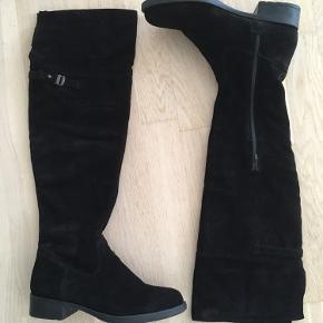 Super lækre sorte overknee læderstøvler fra Tamaris. Behagelig pasform og blødt materiale. Hele overdelen af støvlen er læder (og ikke billigt tekstil som mange overknee har).   Går til ca. midt på knæet - men selvfølgelig afhænging af hvor høj man er. Hælhøjde er ca. cm. 3.  Aldrig brugt. Æske medfølger.