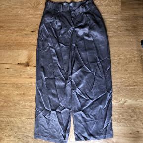 Bukserne kommer med bælte i samme stof.