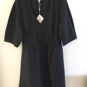 Baum Adarah kjole - i butikkerne nu til fuld pris Skøn minikjole, der fremhæver taljen, med knapper foran og V-udskæring.  Materiale 100% Polyester Lining 100% Viskose Længde i alt92,15 Bryst 98,8 Talje 82 Længde, ærme38,5   VENLIGST LÆS DETTE INDEN DU KONTAKTER MIG  jeg tager ikke billeder med tøjet på   ALLE varer sendes med dao for købers regning.   BEMÆRK ingen bytte eller retur - jeg tilbyder ikke afhentning eller at mødes. Venligst respekter dette - jeg gør ikke nogen undtagelser.