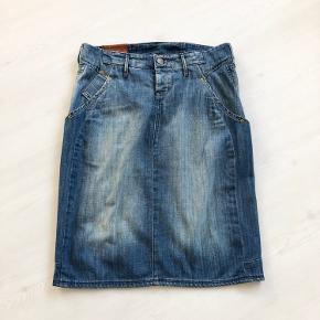 Denim nederdel fra Lee str. S i slidt look.  Der er to forlommer og to baglommer.  Lukkes med en synlig og to skjulte knapper foran.  Fine detaljer i livet.  Længde er 60 cm, og  livvidde er 82 cm.  Fremstillet af bomuld.  Bærer ikke præg af brug.