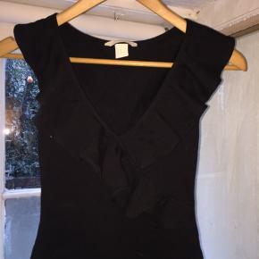 Sort bodystocking, med flæse detaljer ved brystet